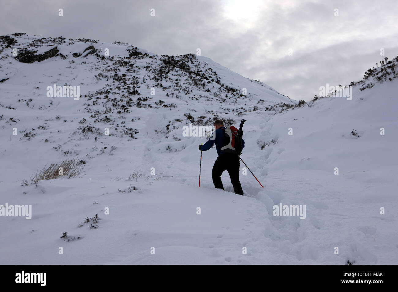 Walker in deep snow on the final ascent to the summit of Ben A'an in the Trossachs - Stock Image