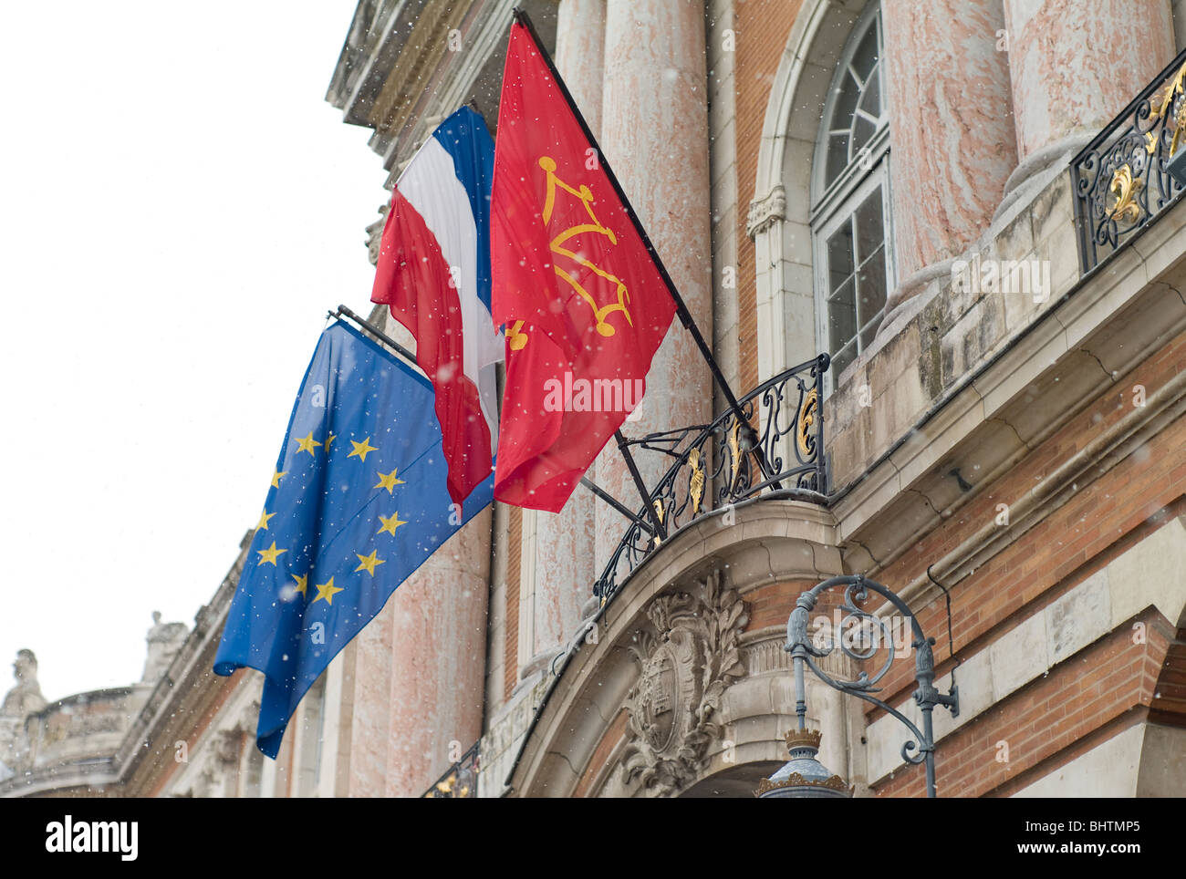 European, French Tricolore and Occitane flags outside the Capitole building, in Toulouse,the regional capital of - Stock Image