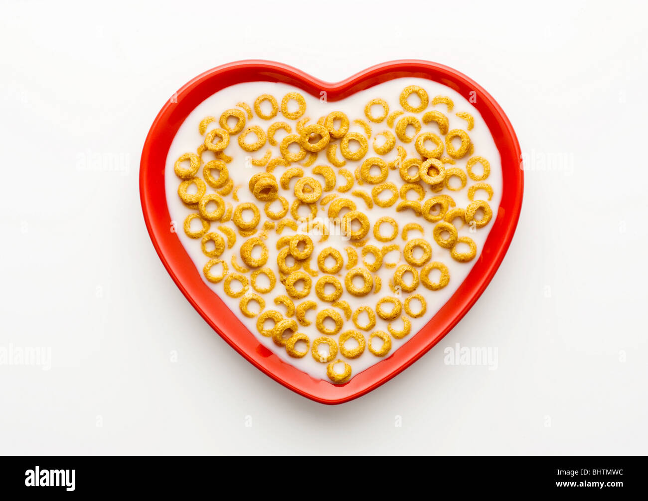 Studio shot of red heart shaped bowl of honey nut loops and milk on a white background, shot from above. - Stock Image