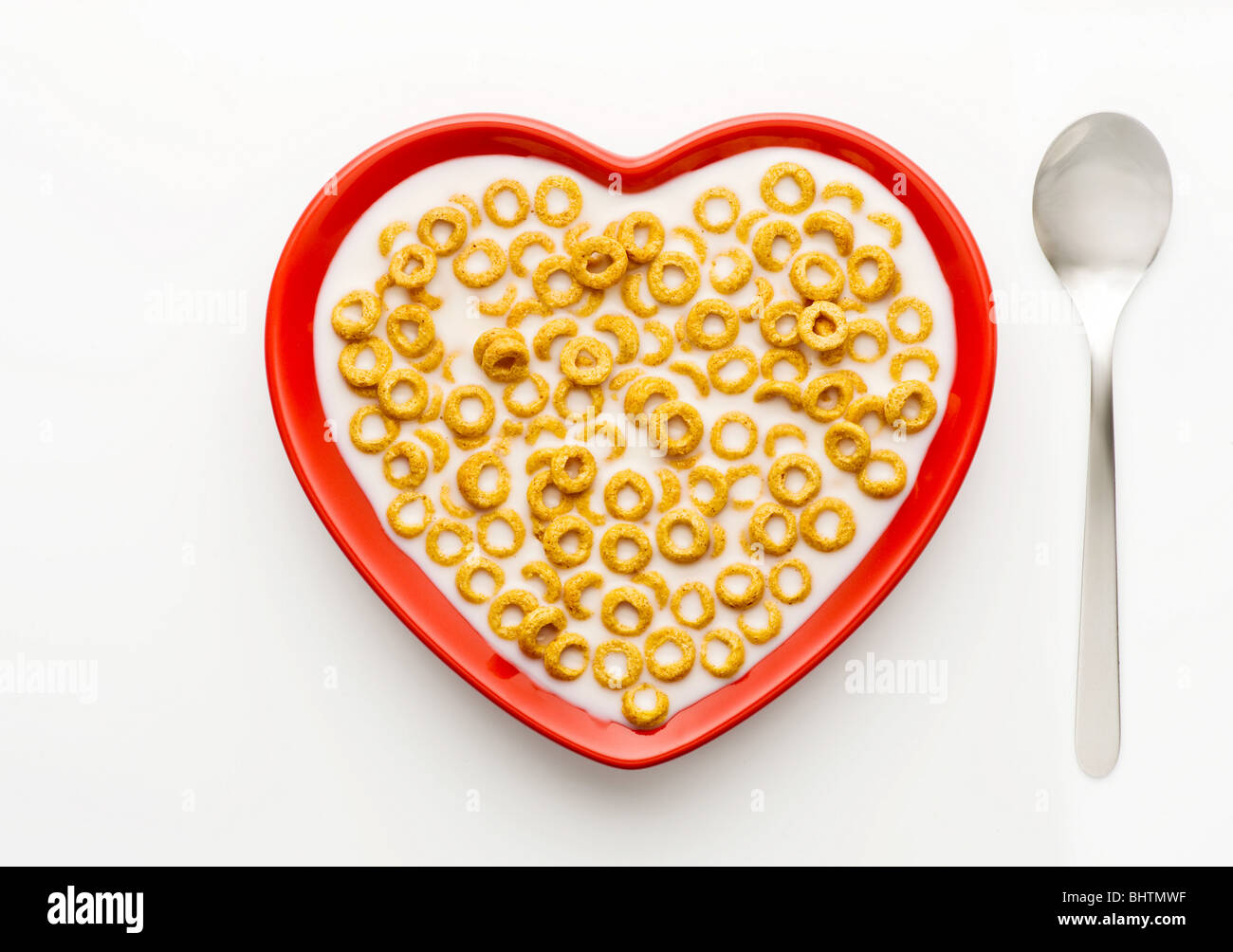 Studio shot of red heart shaped bowl of honey nut loops and milk with a spoon,on a white background, shot from above. - Stock Image