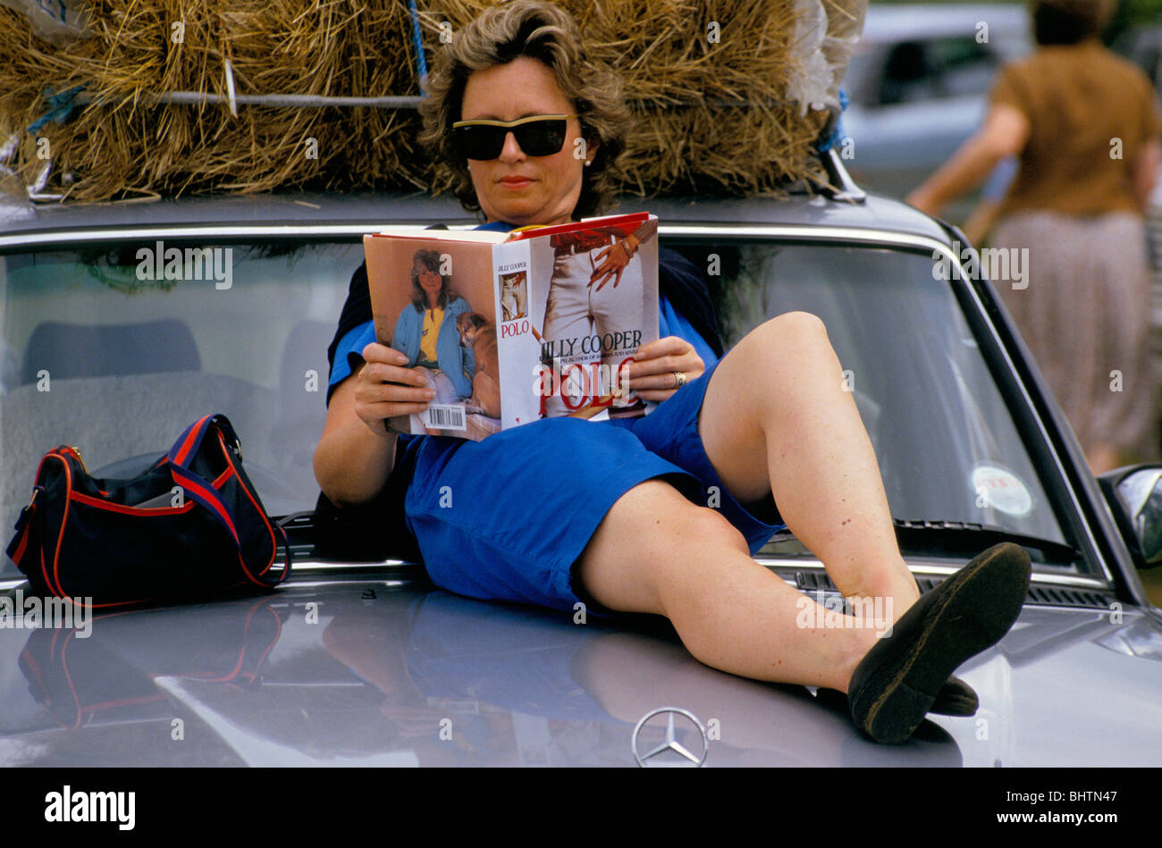 A woman sitting on the bonnet of a Mercedes Car reading a Jilly Cooper polo book during a polo match in the Cotswolds - Stock Image