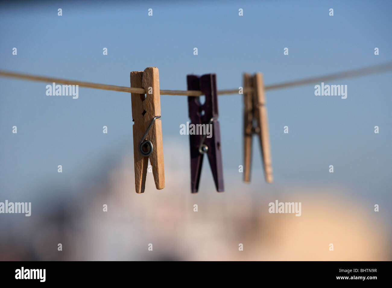 three clothes pegs hanging on a washing line against a bright blue sky over the city - Stock Image