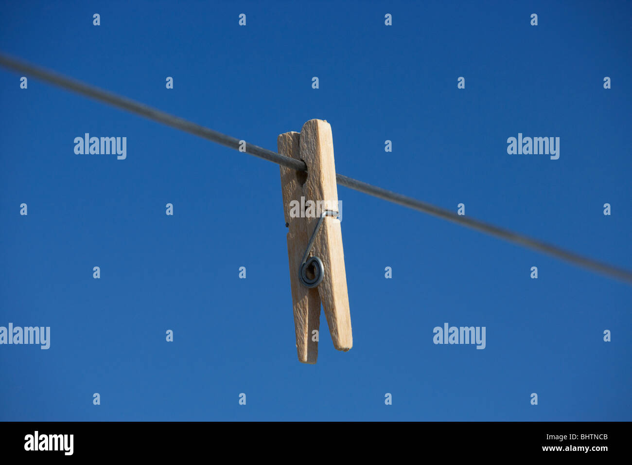 single clothes peg hanging on a washing line against a bright blue sky - Stock Image