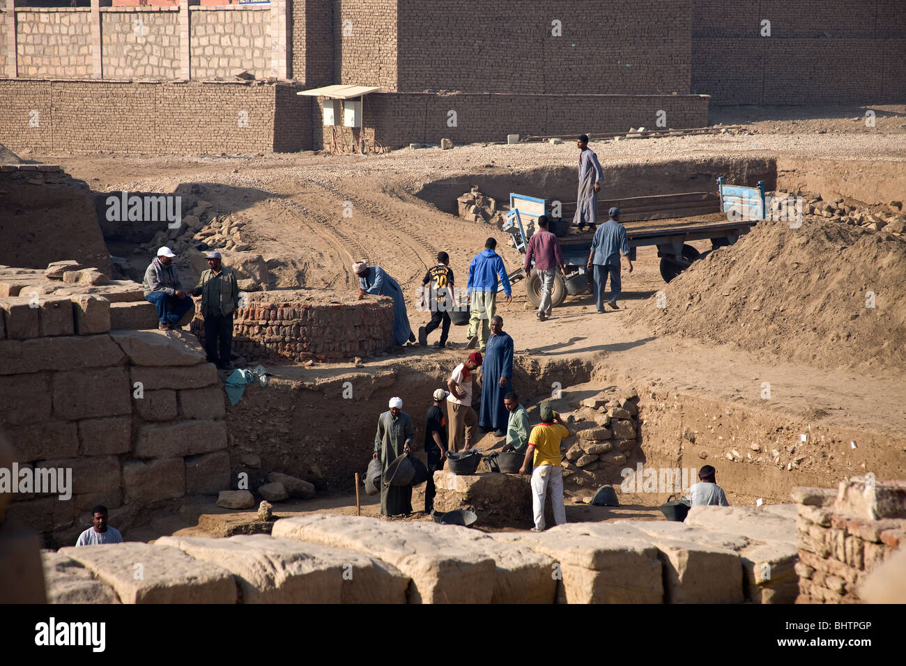 Archaeologists and workers excavating a site at Karnak Temple. - Stock Image