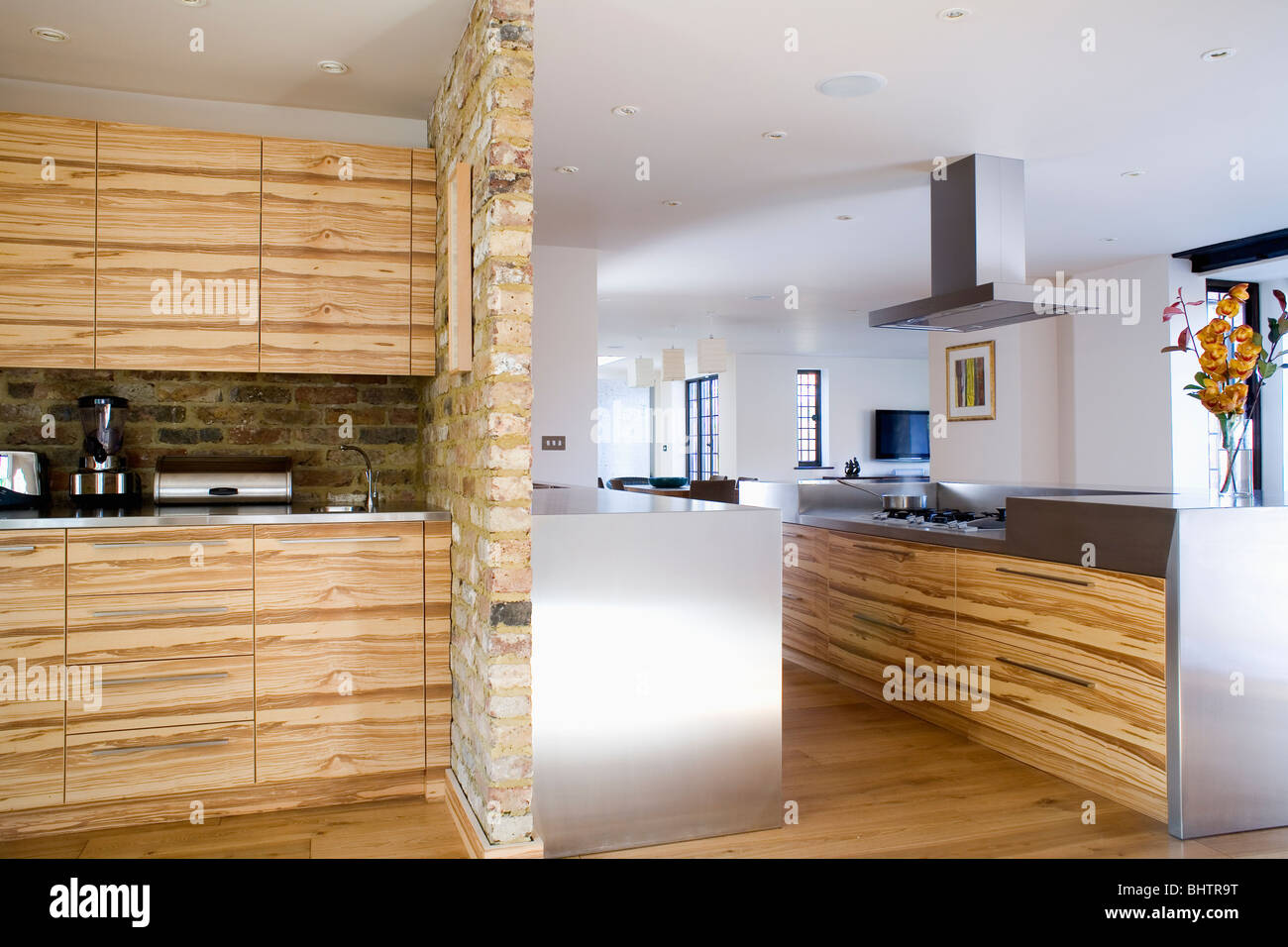 Fitted cupboards with walnut veneer doors beside exposed stone dividing wall in large modern kitchen with