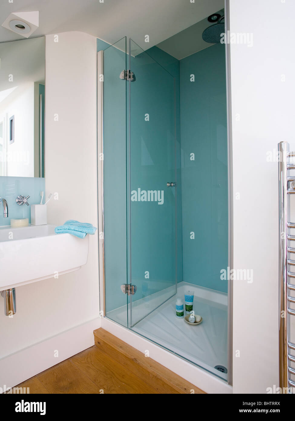 Glass doors on shower with pastel blue mosaic tiled walls in modern ...