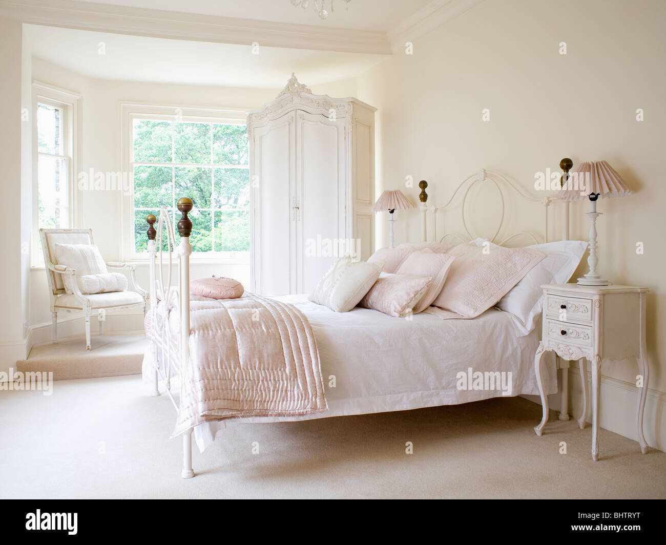 Pale pink silk quilt and white bedlinen on white wrought iron bed in ...