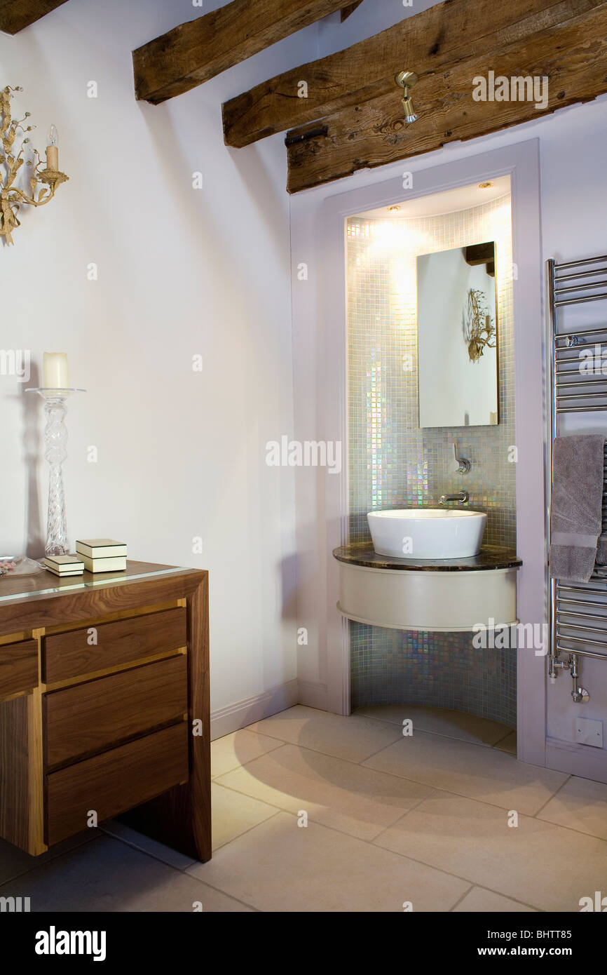 Mirror above basin in curved vanity unit in mosaic tiled alcove in ...