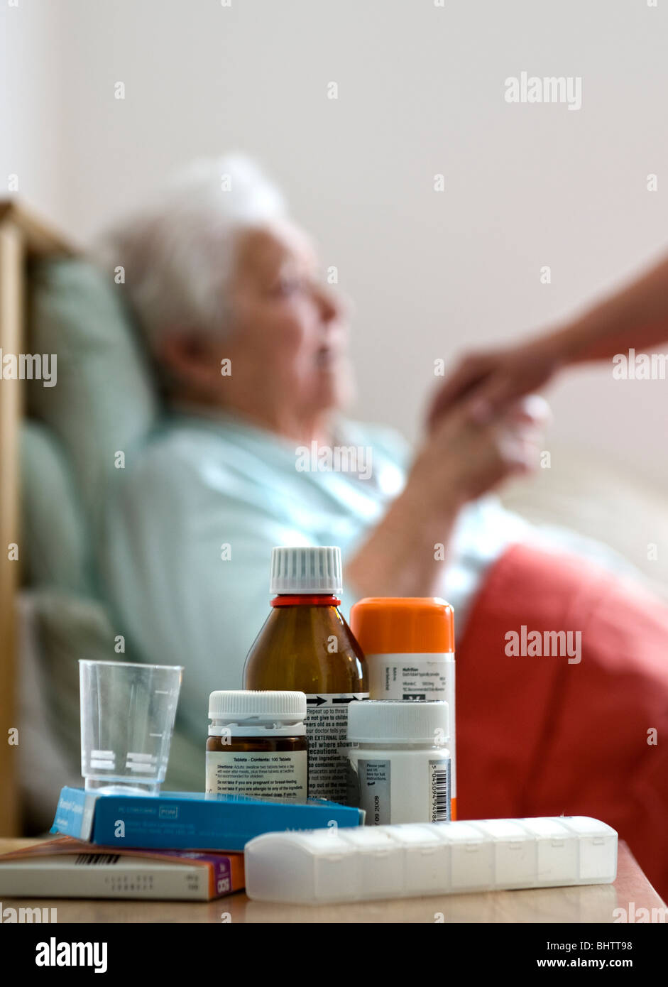 Elderly lady in her bedroom with carer holding her hand, variety of medication in foreground - Stock Image