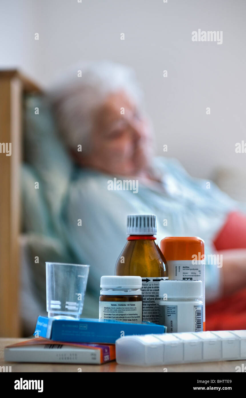 Elderly lady resting in bed in her room with a variety of medication and dispensers in foreground - Stock Image