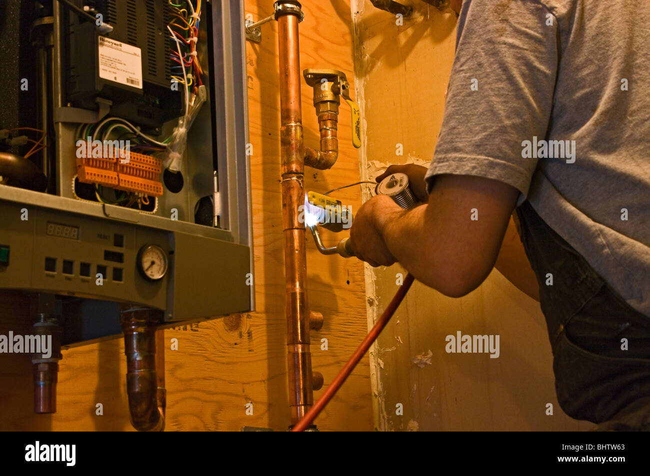 Plumber soldering copper pipes - Stock Image