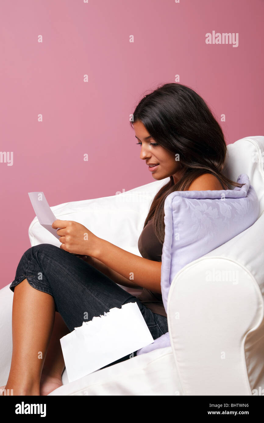 Women sat in an armchair reading a letter, blank envelope if you want to add your own text. - Stock Image