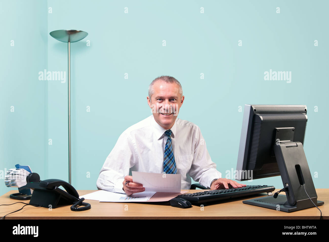 A mature businessman sat at his desk, looking towards camera and smiling. - Stock Image