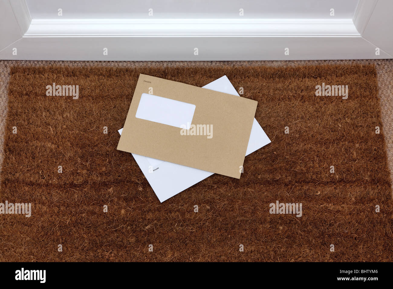 Two envelopes on a doormat, blank window to add your own name and address details. - Stock Image