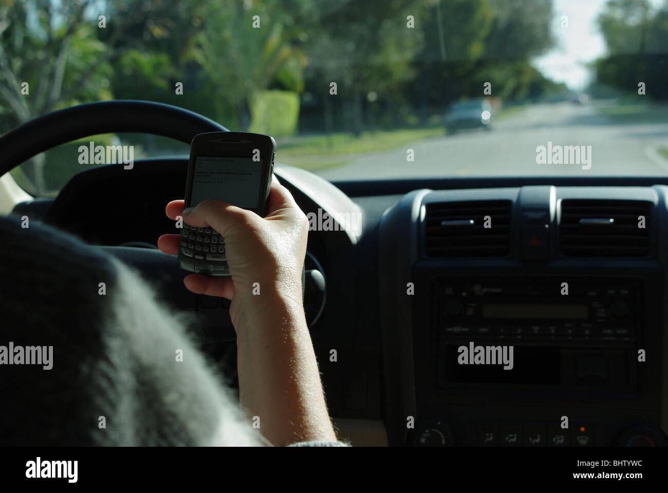 Woman is using  PDA to check and type text messages while driving her car - Stock Image