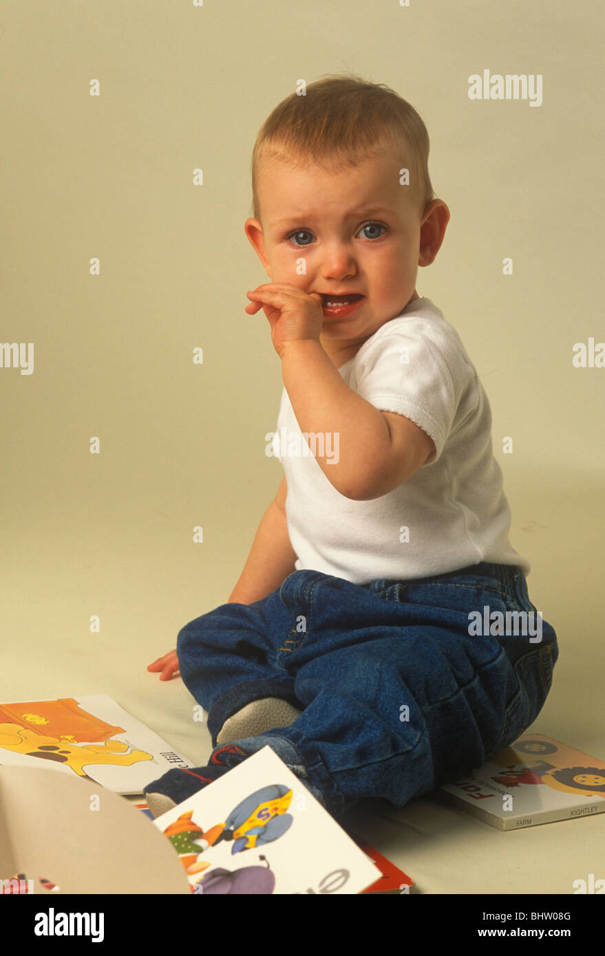 baby of nine months looking worried and tearful - Stock Image