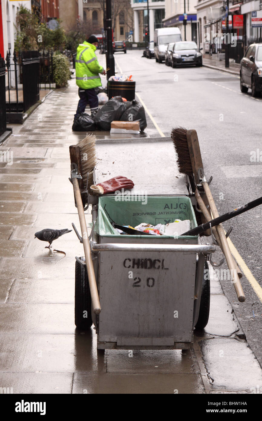 London council street cleaning services dust cart and street sweeper employee Stock Photo