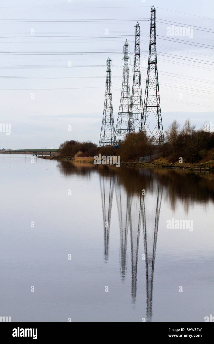 Electric pylons reflected in the River Ribble; Preston; Lancashire - Stock Image