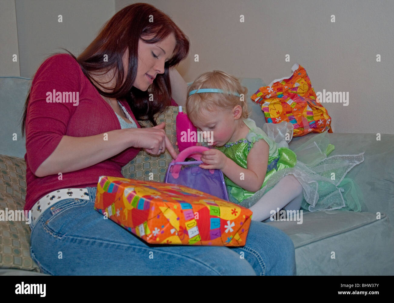 This Young Mother Is Helping Her Cute 2 Year Old Caucasian Toddler Daughter With Birthday Presents Background Intentionally