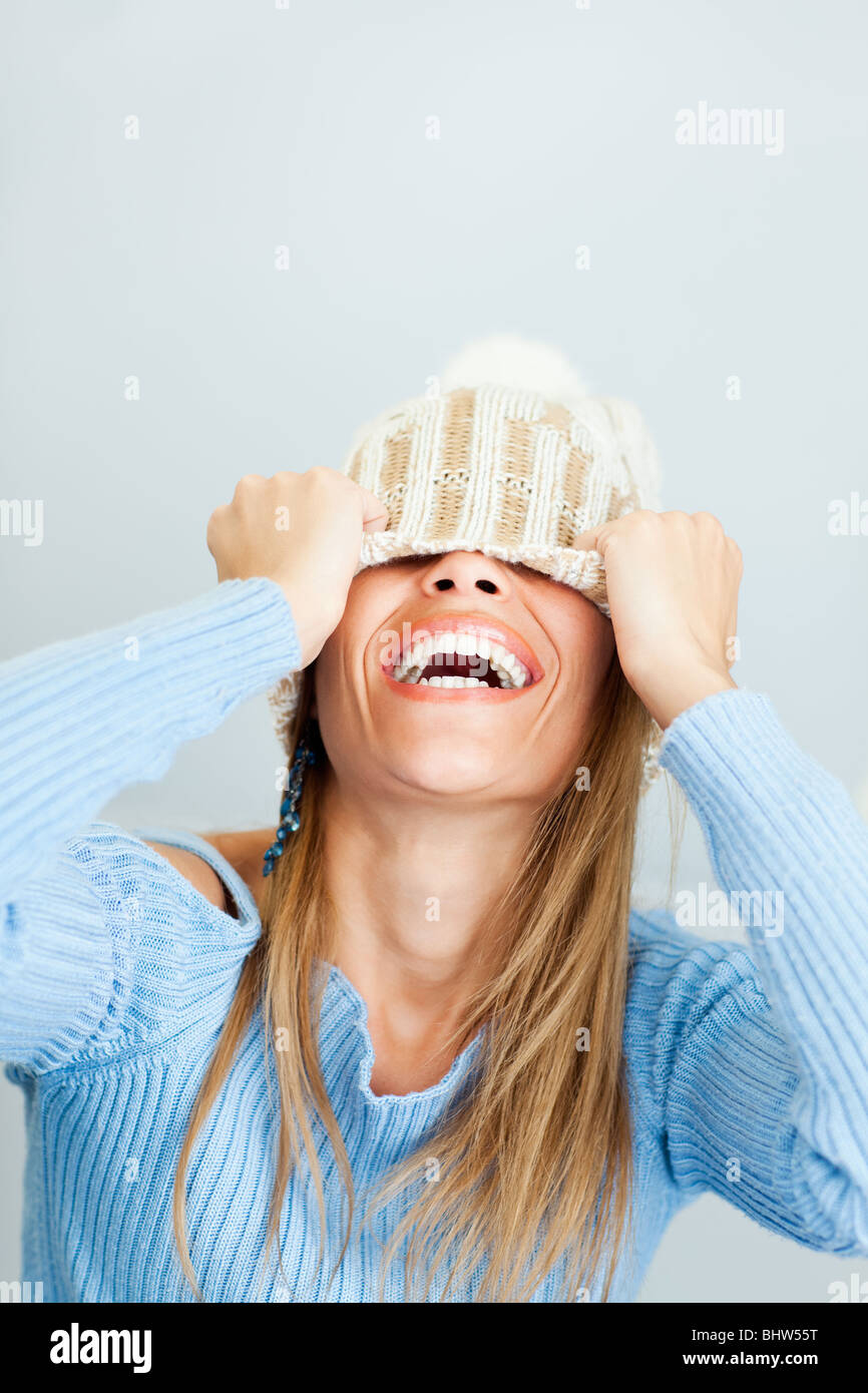 portrait of young woman laughing while covering face with wool hat. Vertical shape, Copy space - Stock Image
