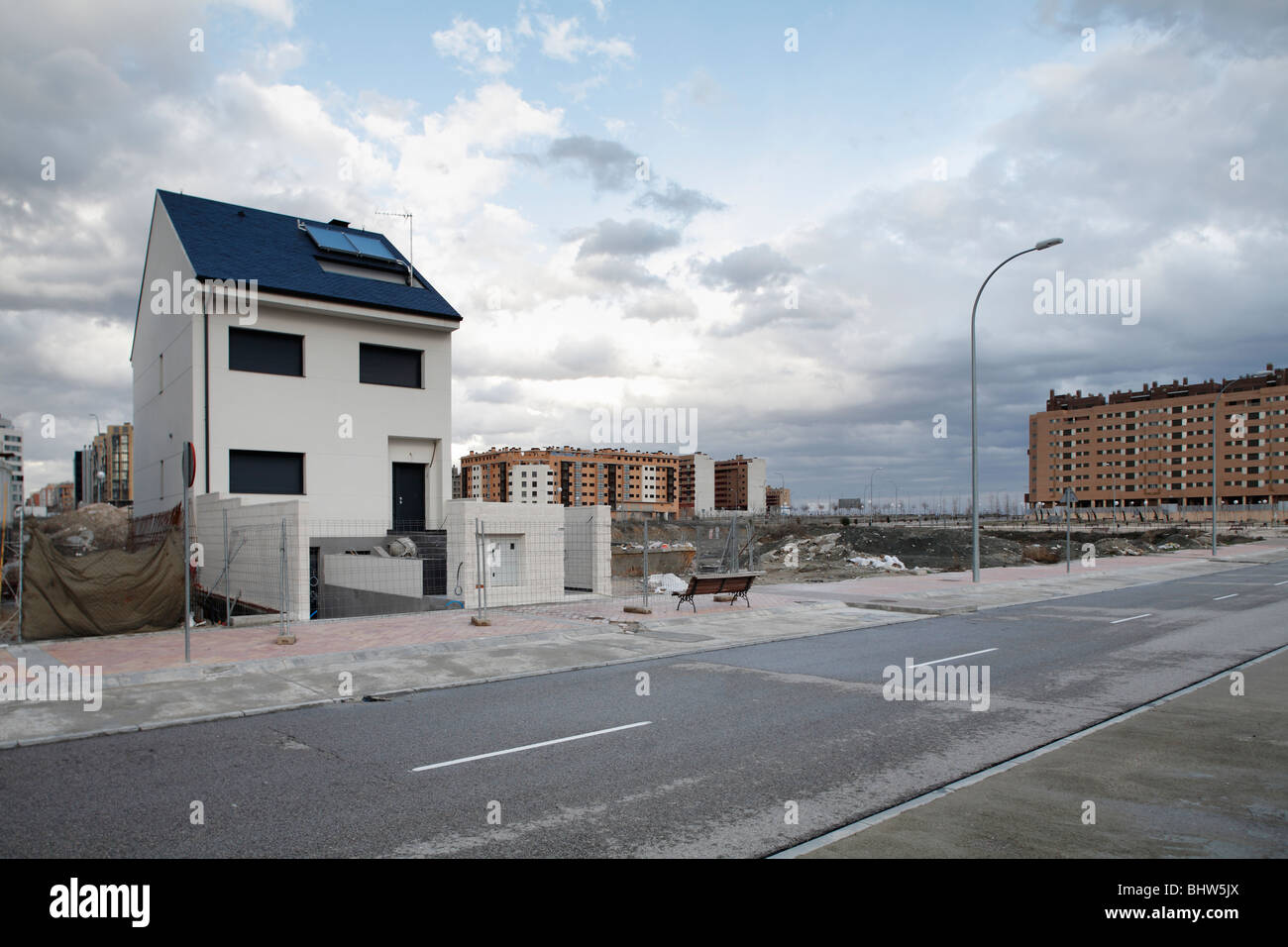 Unsold house stands amidst unoccupied new blocks of flats on the outskirts of Madrid. - Stock Image