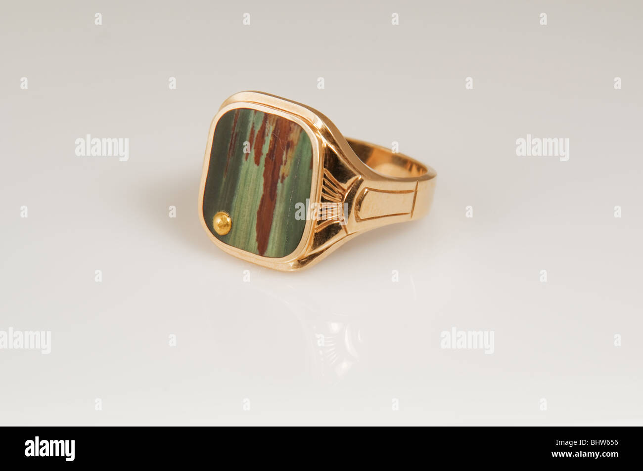 This man's gold ring has a picture agate in green and brown tones with a gold dot to the side isolated on a - Stock Image