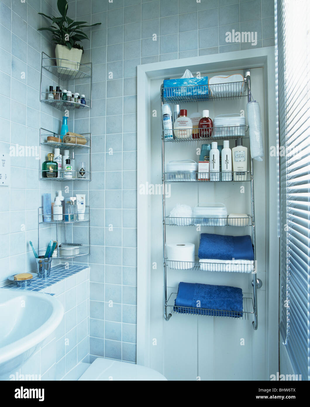 Bottles of toiletries and towels on stainless-steel shelves in ...