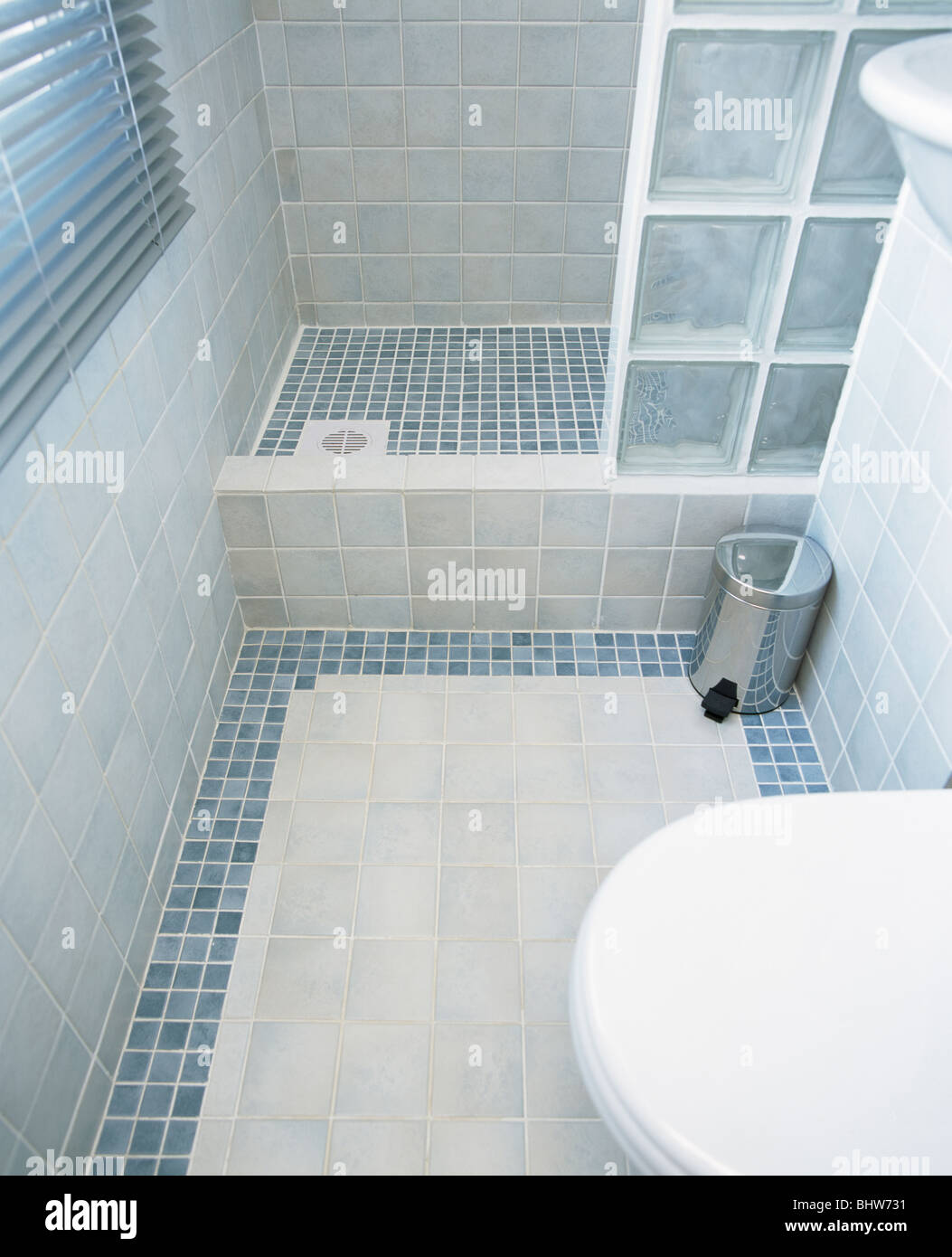 Modern tiled bathroom with glass brick shower wall and blue mosaic ...