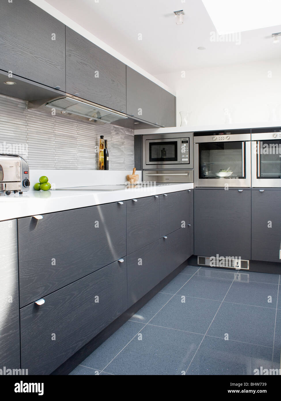grey ceramic floor tiles in modern white kitchen with dark gray