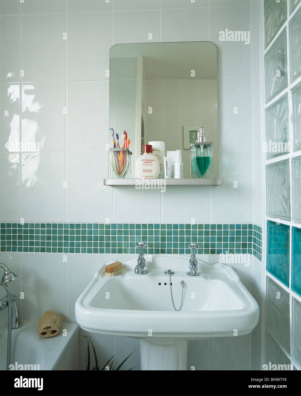 Mirror above green mosaic-tiled border above basin in small modern ...