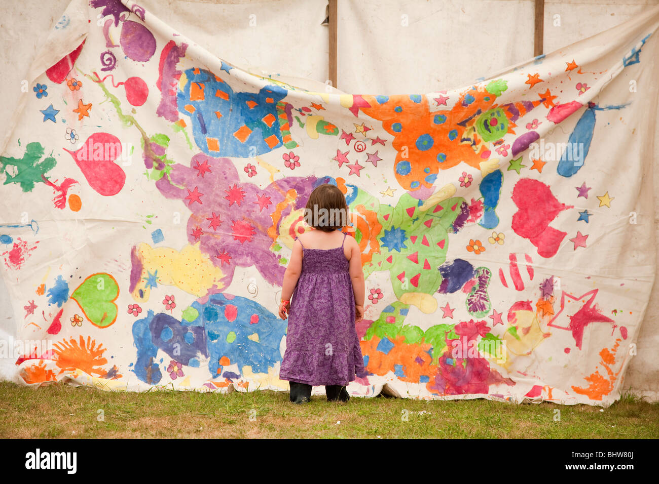 A toddler admires artwork at the Latitude Festival 2009. Children can be art critics too. - Stock Image