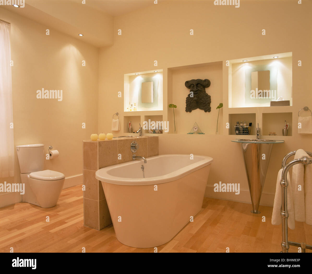 Freestanding bath against low tiled iding wall in modern white bathroom with down-lighting and alcove shelving & Freestanding bath against low tiled iding wall in modern white ...