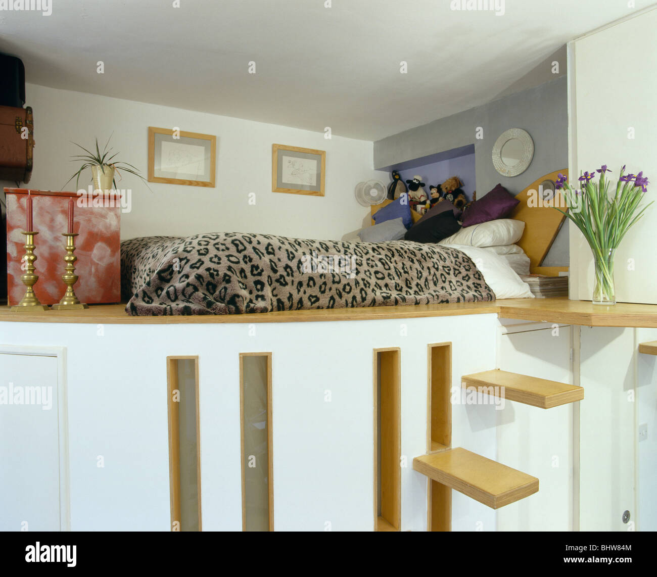 Steps up to platform bed with animal-print bed-cover in small studio apartment bedroom & Steps up to platform bed with animal-print bed-cover in small studio ...