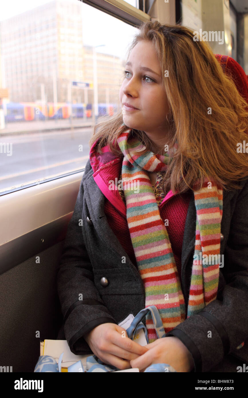 Teenage girl aged age 16 17 years old traveling on train looking confident - Stock Image