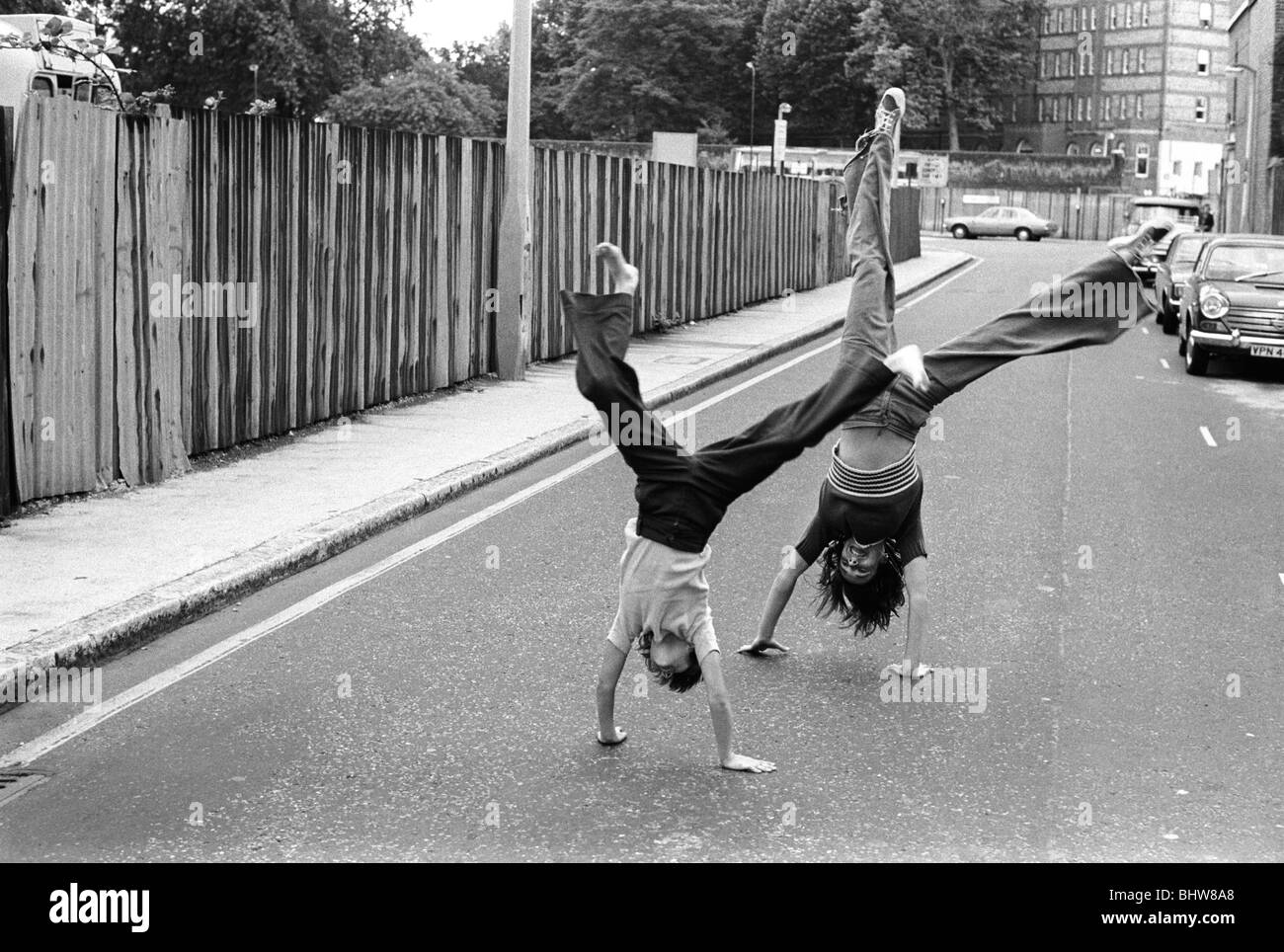 Teenage girls playing turning cartwheels in the street. Elephant and Castle South London 1970s UK 1975 HOMER SYKES - Stock Image