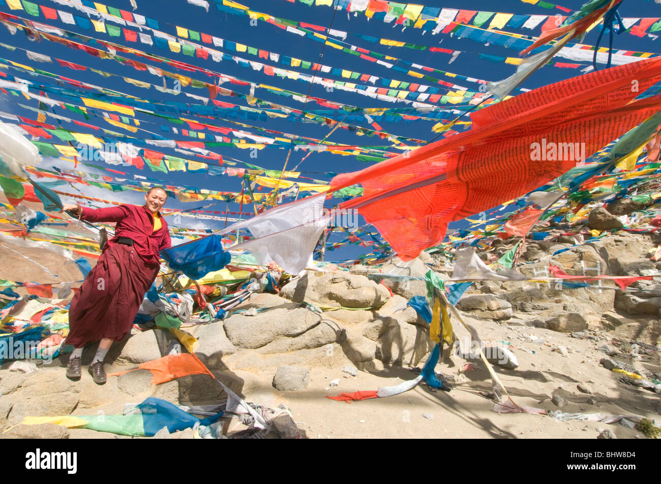 A Buddhist monk standing next to prayer flags in Tibet - Stock Image