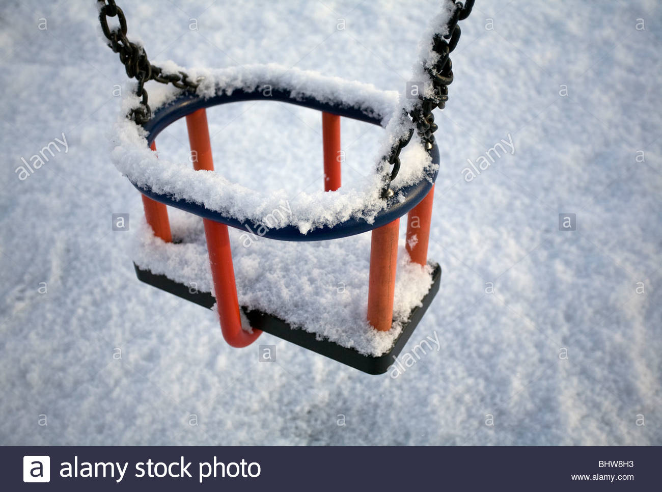 Snow covers a child's swing in a park. - Stock Image