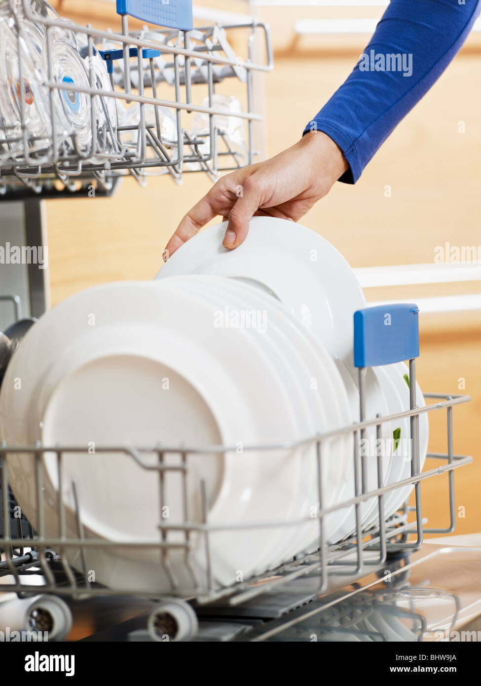 close up of woman in kitchen using dishwasher - Stock Image