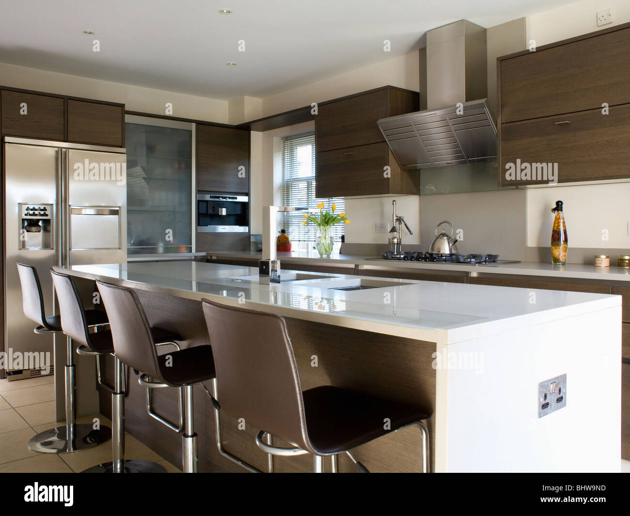 Black Stools At Breakfast Bar On White Island Unit In Modern Kitchen Stock Photo Alamy
