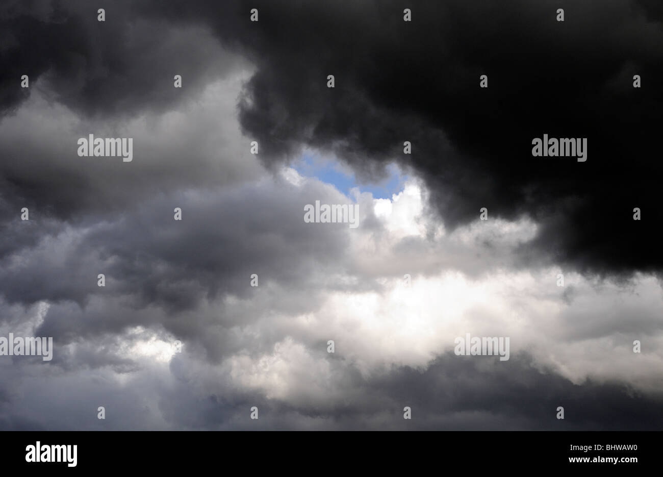 A patch of blue sky shows through black and grey thunder clouds. Bedgebury Forest, Kent, UK. - Stock Image