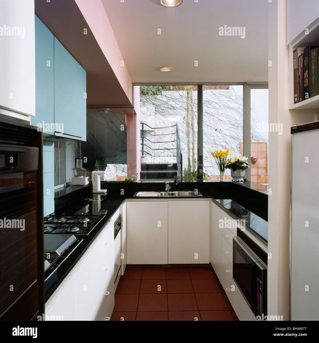 Black Worktops In Modern Kitchen With Pale Blue And White