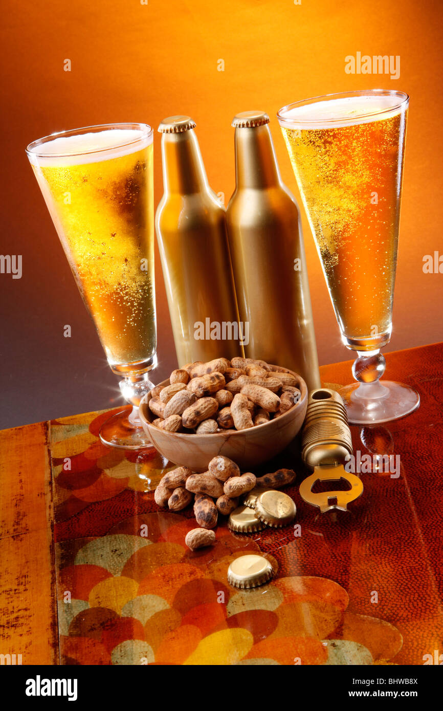 Golden beer, roasted peanuts, opener and caps - Stock Image