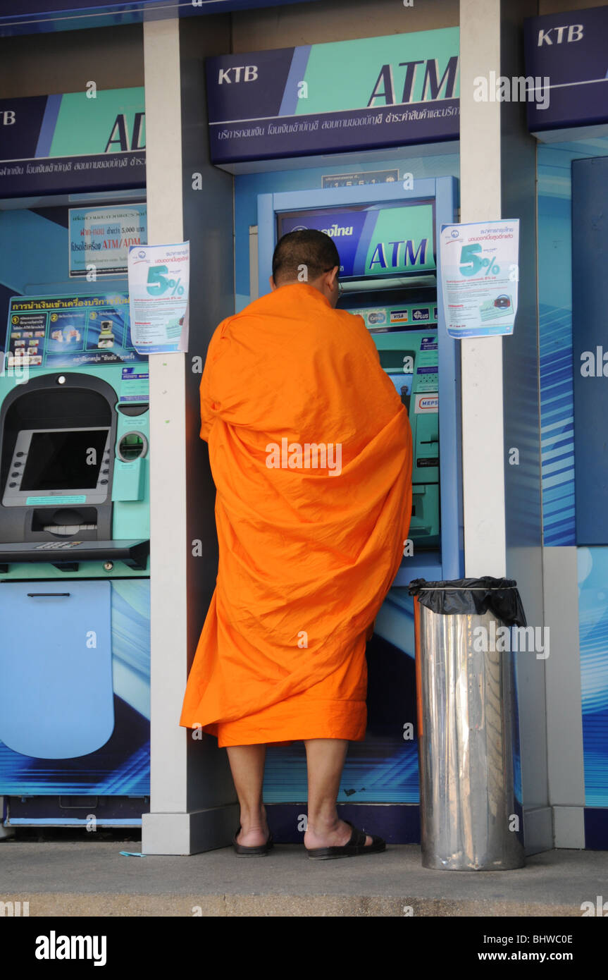 A Buddhist monk using an ATM in the bustling Old City of Chiang Mai, northern Thailand. - Stock Image