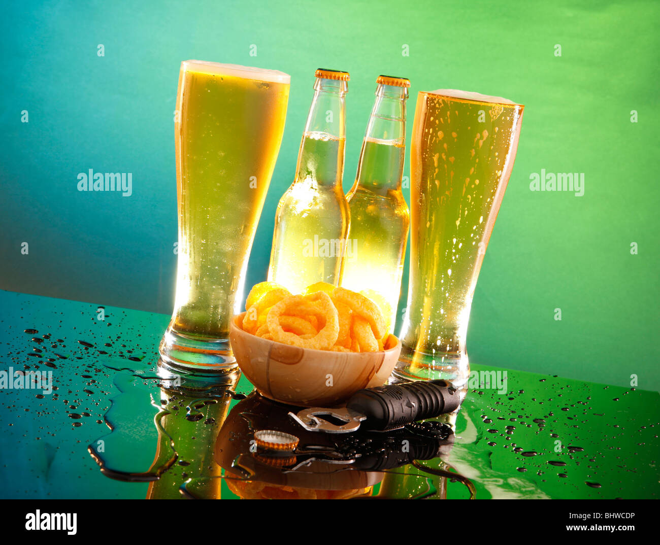 A couple of tall cool beers with bottles, onion ring snacks and a cap opener - Stock Image