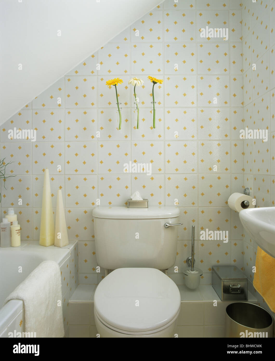 Small economy-style attic bathroom with yellow-patterned white tiles ...
