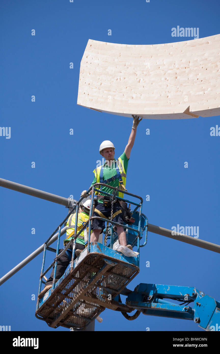 High level Construction workers building laminated wood wave roof on Mountbatten centre in Portsmouth - Stock Image