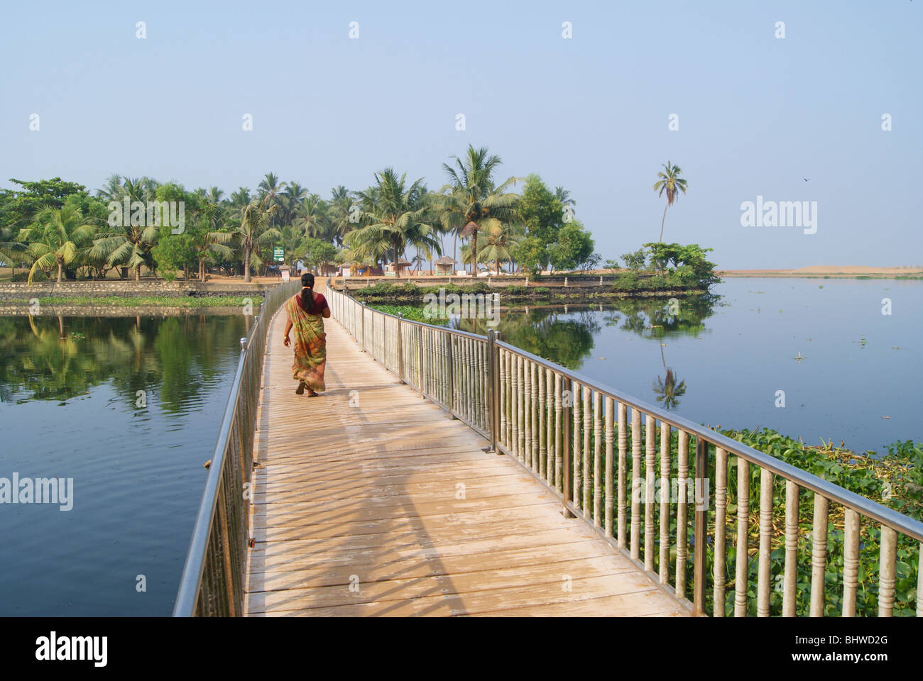 Woman Walking through the Beautiful floating wooden bridge in Veli Tourist Village surrounded by Kerala Backwaters - Stock Image