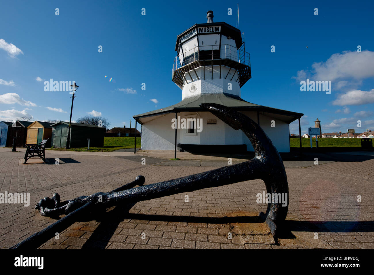 The Low Lighthouse with anchor at the port of Harwich, Essex, UK. Built in 1818 it is now home to the Maritime Museum. - Stock Image