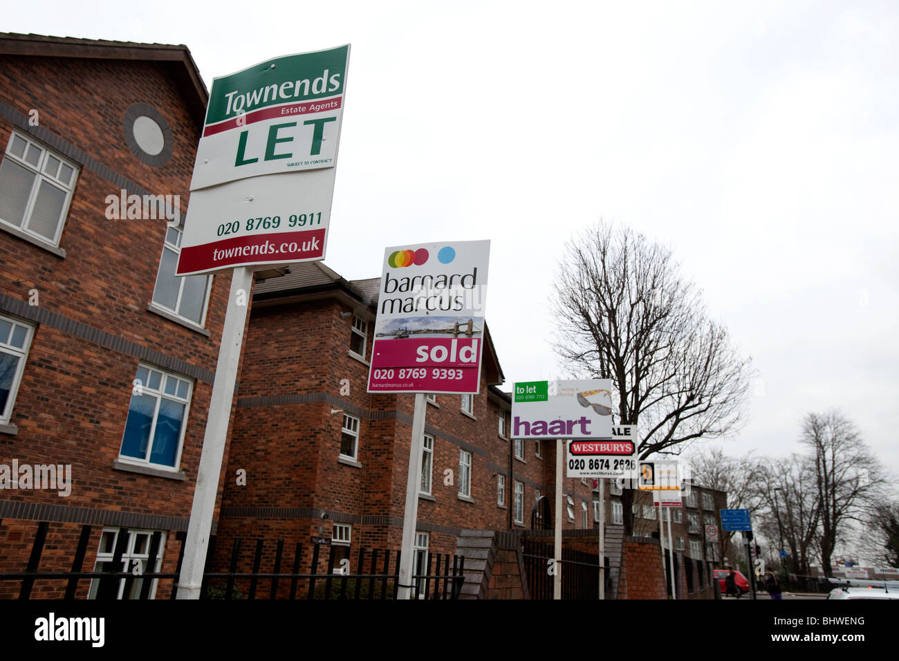 Estate agents sales and lettings boards line in street - Stock Image