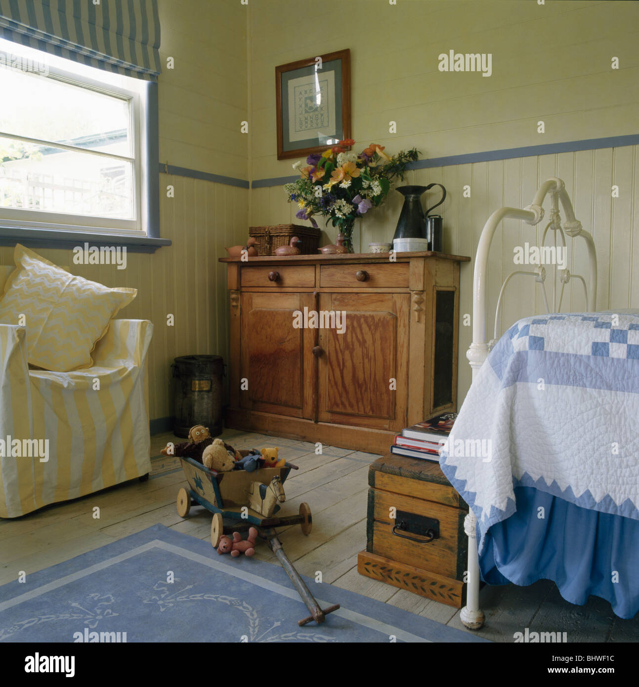 Wooden Cupboard And Yellow Striped Chair In Childu0027s Bedroom With Blue+white  Patchwork Quilt On White Cast Iron Bed